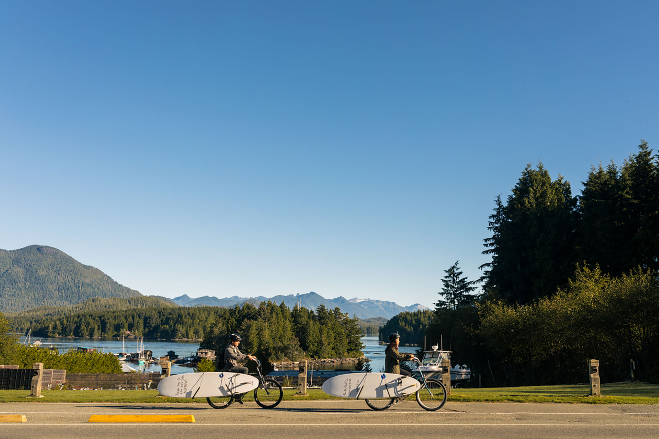 A couple with bikes from Tofino Bike Companyon their way tosurf lessons with Pacific Surf Company | Destination BC/Jordan Dyck